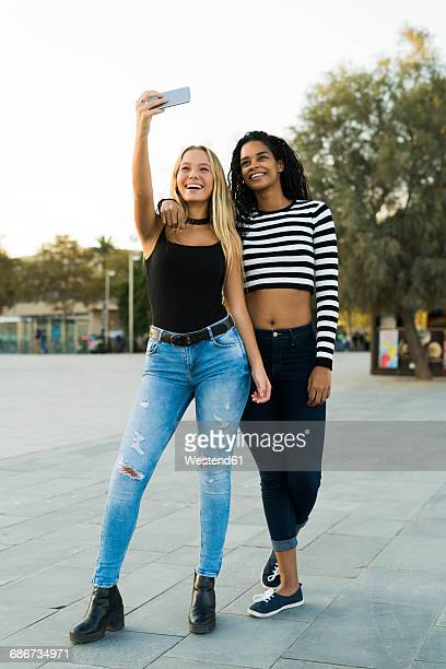 Two young women taking a selfie on square