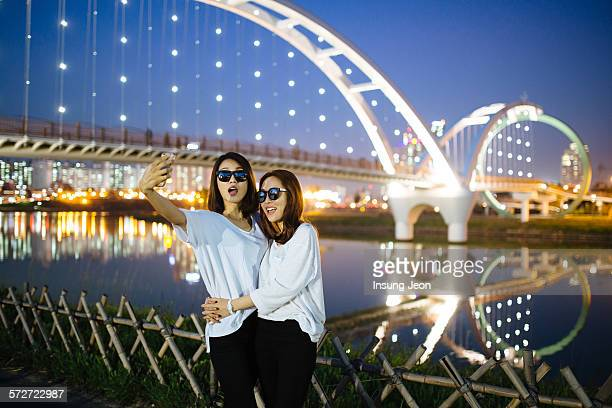 Two young women taking photograph in park