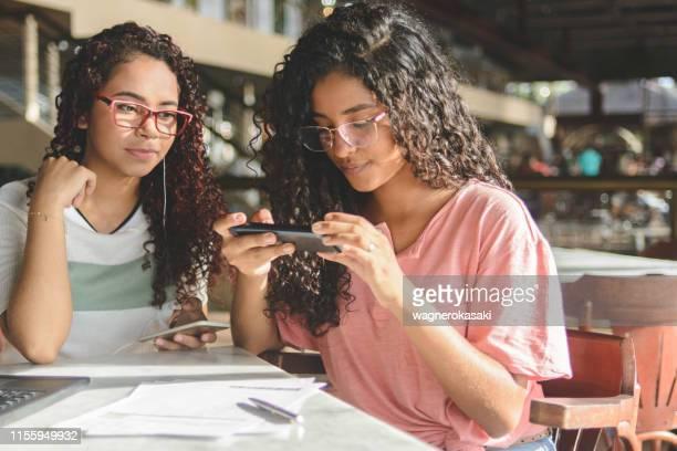 dos mujeres jóvenes tomando fotos en el teléfono inteligente de código de barras para el pago de facturas a través de la aplicación de banca en línea - hispanoamérica fotografías e imágenes de stock