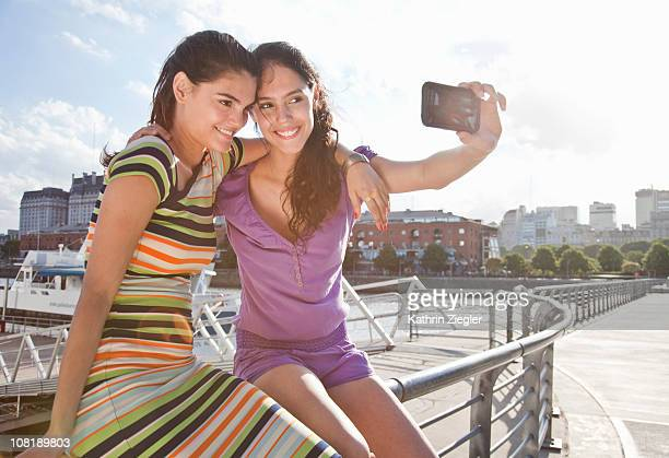 two young women taking picture with smart phone