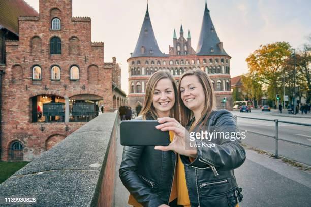 two young women taking self portrait - sleeswijk holstein stockfoto's en -beelden