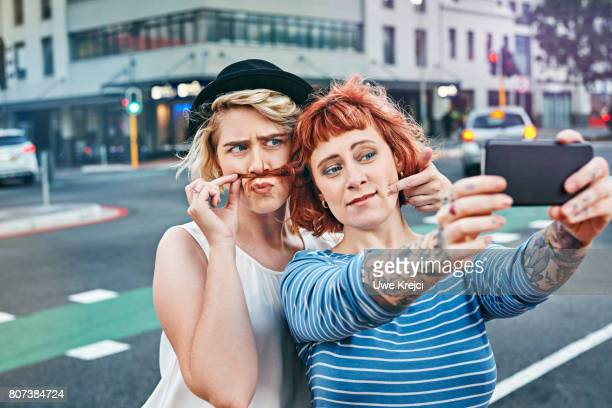 two young women taking self portrait - dyed red hair stock pictures, royalty-free photos & images