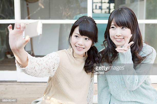 Two young women taking self portrait with smart phone