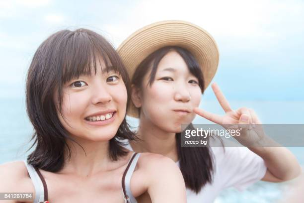two young women taking selfie on the beach - photographing self stock pictures, royalty-free photos & images