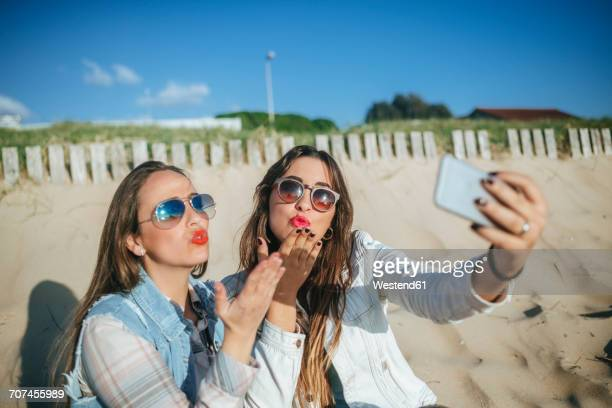 Two young women taking selfie on the beach while blowing a kiss
