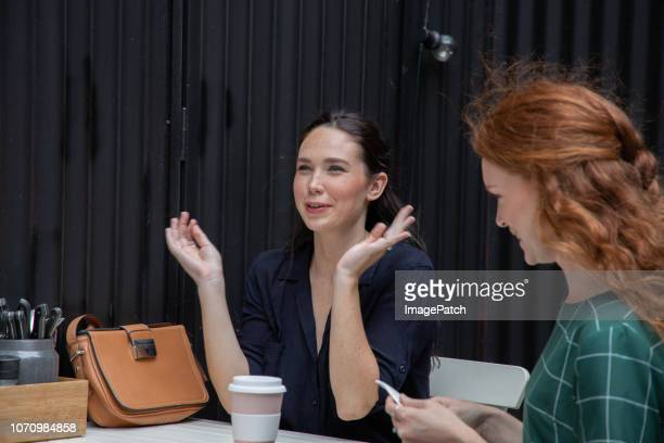 Two young women talking and enjoying coffee together