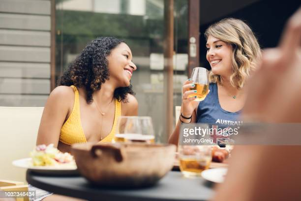 Two young women talking and smiling with beer and food outdoors