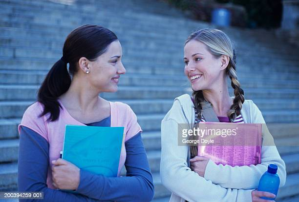 Two young women talking by steps holding folders, smiling