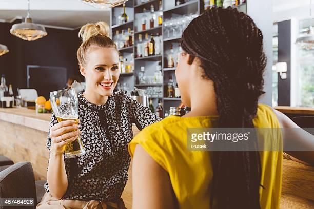 Zwei junge Frauen reden in einem pub