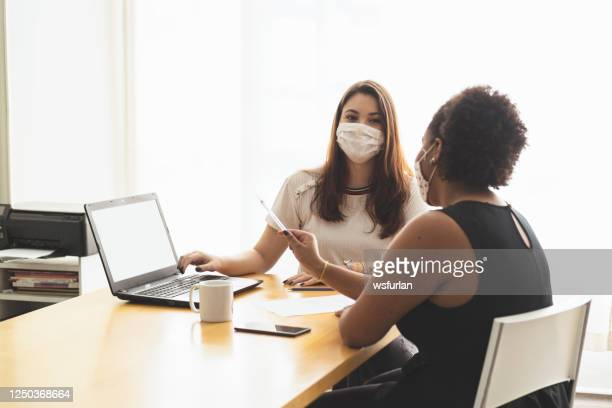 two young women talking in an office wearing a protective face mask. - employee engagement stock pictures, royalty-free photos & images