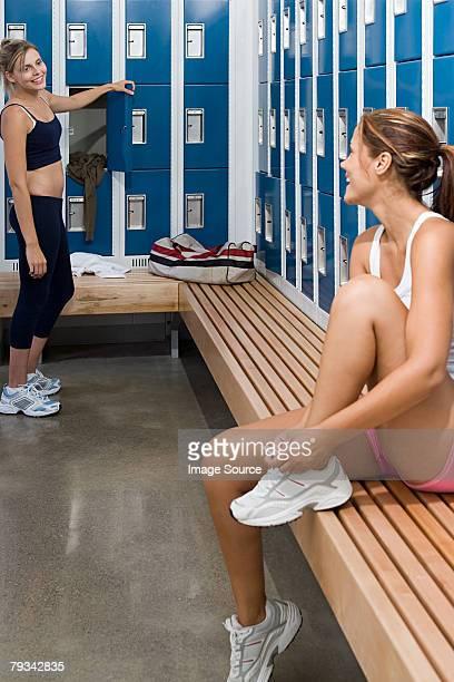 Two young women talking in locker