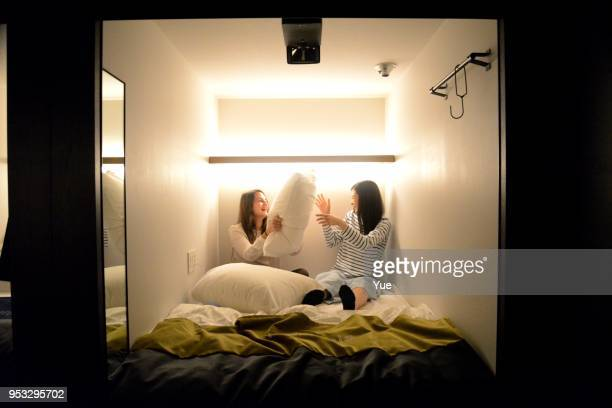 two young women talking on bed of capsule hotel - hostel stock pictures, royalty-free photos & images