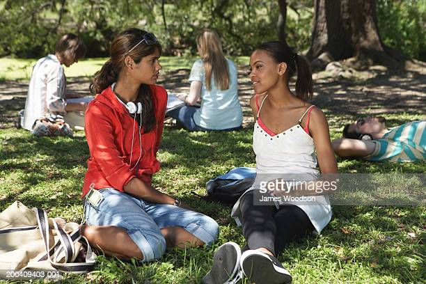 two young women talking on grass, close-up - rolled up trousers stock pictures, royalty-free photos & images