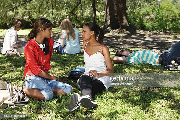 two young women talking on grass - rolled up trousers stock pictures, royalty-free photos & images