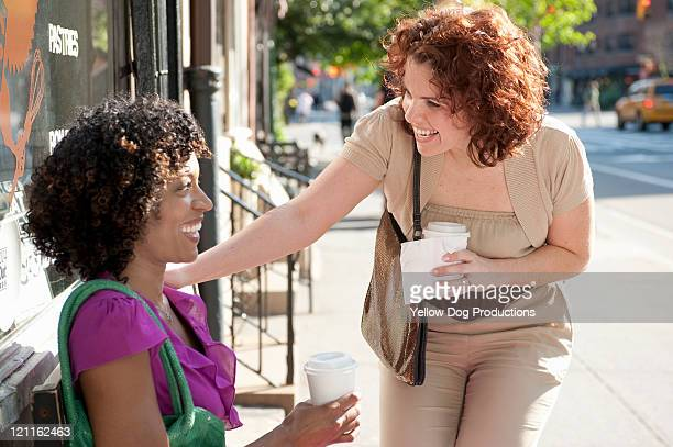 Two young women talking outside cafe