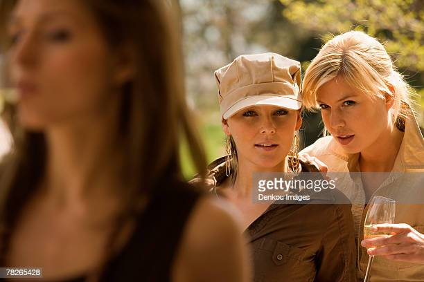 Two young women talking with another young woman in the foreground