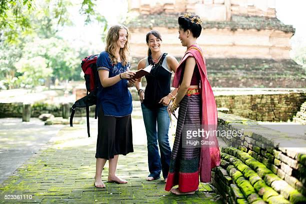 two young women talking with thai woman during their travel to asia, chiang mai, thailand - hugh sitton fotografías e imágenes de stock