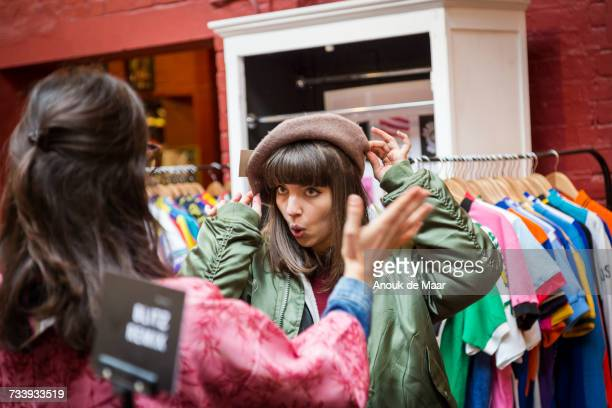 two young women trying on beret at vintage clothes stall - clothing stock pictures, royalty-free photos & images