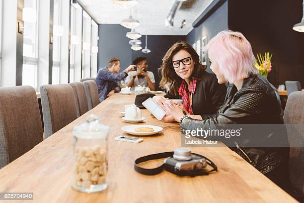 Two young women using digital tablet in a coffee shop
