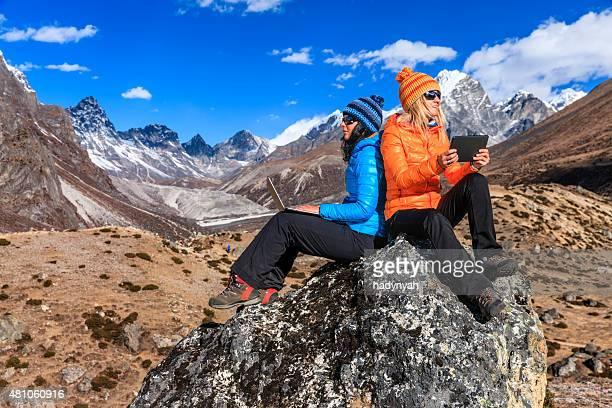 Dos mujeres jóvenes con ordenador portátil y tablet en Himalayas, Nepal