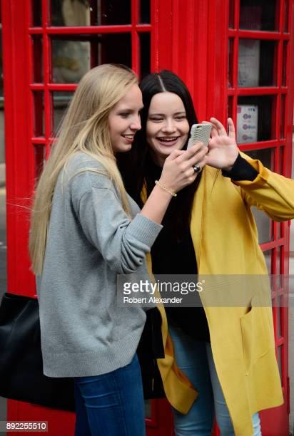 Two young women visiting London England's Covent Garden district take souvenir photographs using one of the city's iconic red telephone booths as a...