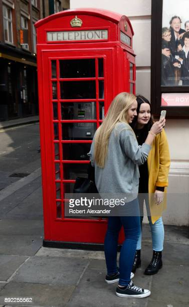 Two young women visiting London, England's Covent Garden district take souvenir photographs using one of the city's iconic red telephone booths as a...