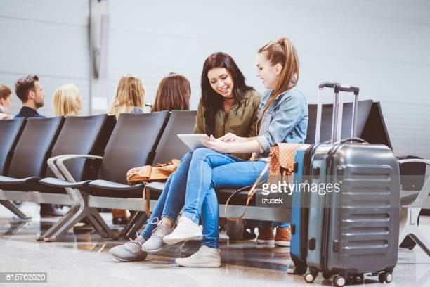 zwei junge frauen warten auf ihren flug und mit digital-tablette - izusek stock-fotos und bilder