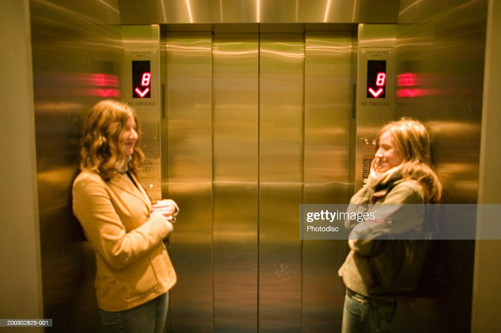 Two young women waiting in elevator : Stock Photo