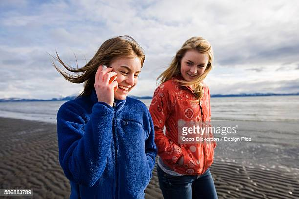Two Young Women Walk Along Bishops Beach In Homer, Alaska While One Talks On A Cell Phone