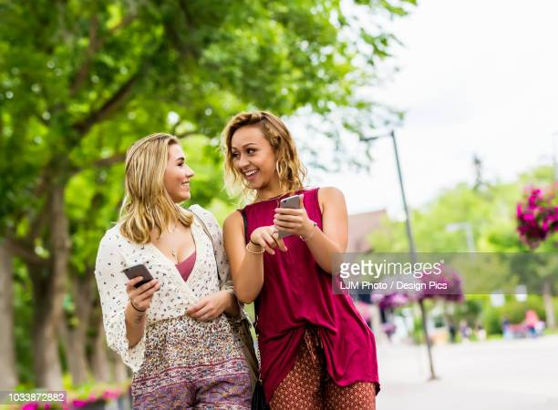 Two young women walk down a path on a university campus laughing and talking together as they look at their smart phones