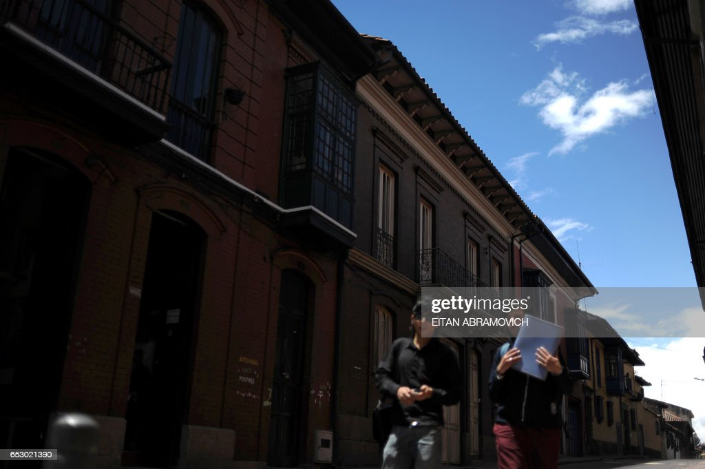 Two young women walk down a street in the historic neighborhood of La Candelaria in Bogota on September 17, 2009. La Candelaria is Bogota's oldest neighbourhood and the city's historical center, known for its colonial houses with wooden balconies and clay shingle roofs. AFP PHOTO/Eitan Abramovich /
