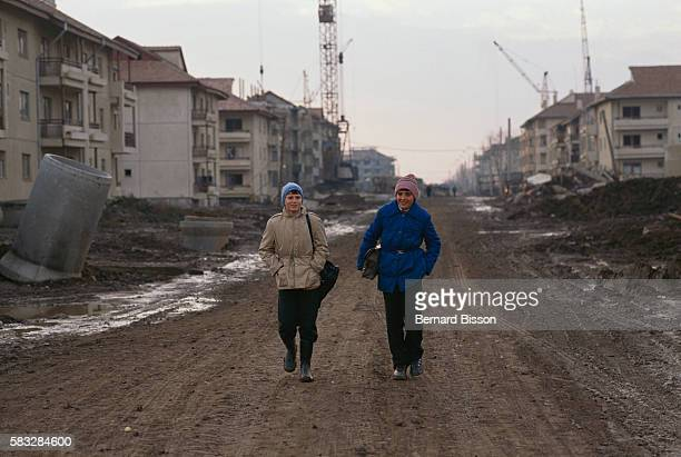 Two young women walk in an unpaved street in Bucharest, on November 21, 1989. Poverty and harsh conditions are part of daily life for Romanians under...