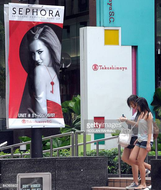Two young women walk out of a shopping centre past a promotional poster for cosmetics and skin scare products in Singapore on January 13 2009 An...