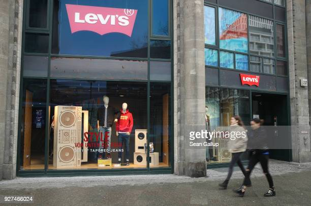 Two young women walk past a Levi's jeans and clothing store on March 5 2018 in Berlin Germany Tensions between US President Donald Trump and the...