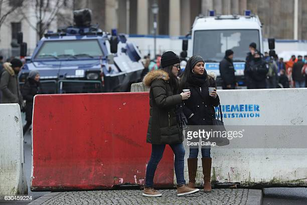 Two young women walk past concrete security barriers and a police armoured vehicle near the Brandenburg Gate prior to a concert there on December 23...