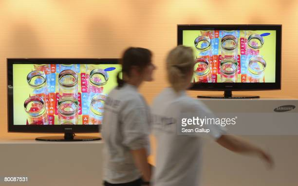 Two young women walk past high definition LCD displays at the Samsung stand at the CeBIT technology fair a day before the fair's official opening on...