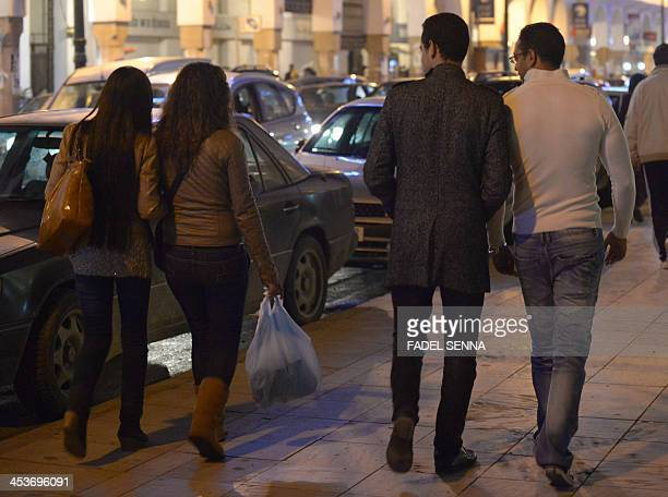 BROUSKY Two young women walk past men who look and talk to them in Rabat on November 24 2013 A longawaited law to combat violence against women is...