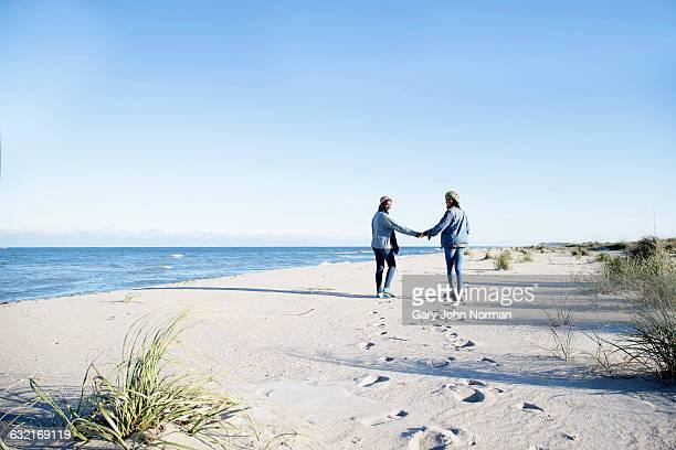 Two young women, walking along beach, holding hands, rear view