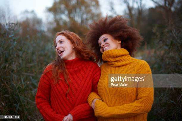 Two young women, walking arm in arm along rural pathway