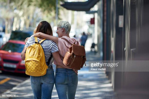 Two young women walking arm in arm, down street