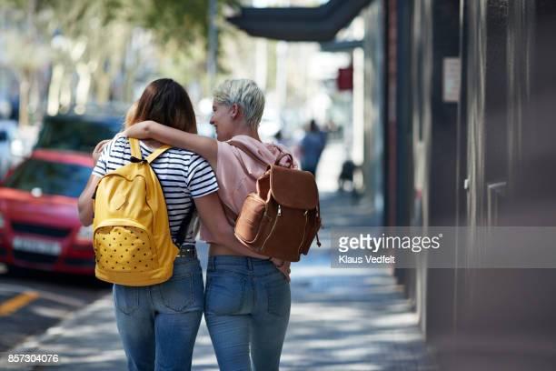 two young women walking arm in arm, down street - lesbische stockfoto's en -beelden