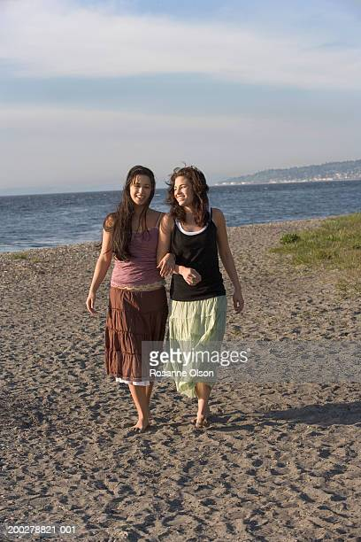 Two young women walking arm-in-arm on beach, smiling
