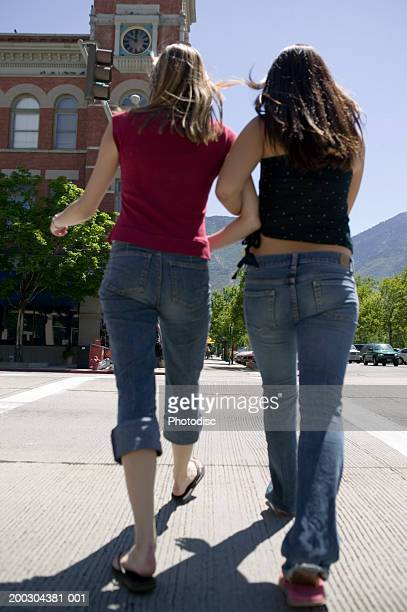 Two young women walking down street of city