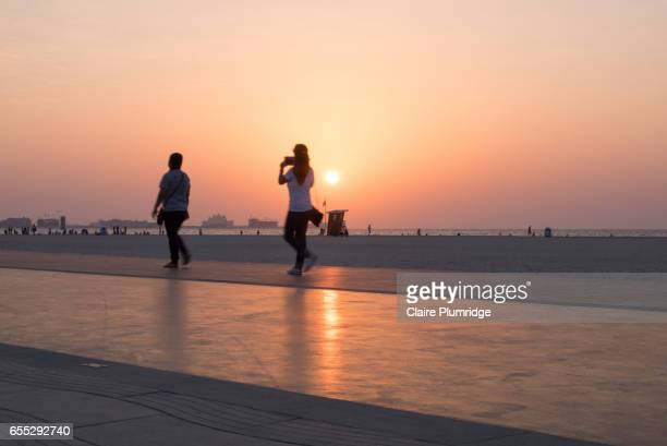 two young women  walking on a purpose built walking/running track on a beach in dubai at sunset - claire plumridge stock pictures, royalty-free photos & images