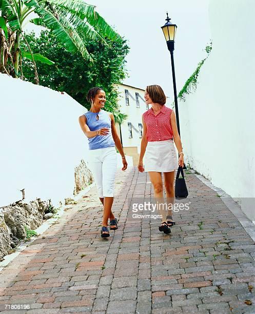 Two young women walking on a street, Bermuda