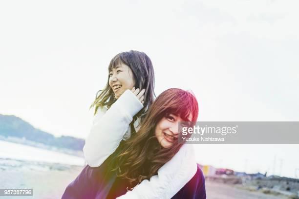 two young women walking together on sandy beach - yusuke nishizawa bildbanksfoton och bilder