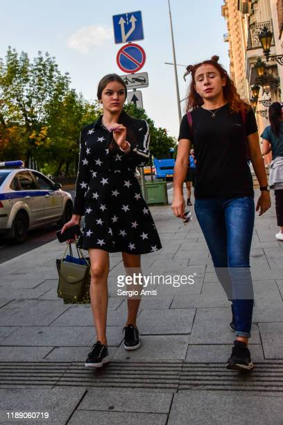two young women walking towards the camera on a pavement in moscow, russia - sergio amiti stock pictures, royalty-free photos & images