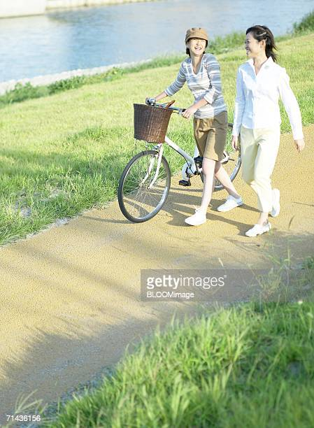 Two young women walking with bicycle and talking