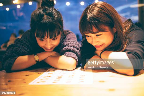two young women watch a meal menu - カフェ ストックフォトと画像