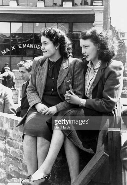 Two young women watching a game of cricket being played by office boys on the bombed site of the Morning Advertiser newspaper offices in Shoe Lane...
